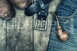Detail of worn blue jeans and brown shoes on a wooden background