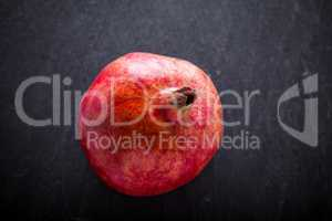 Fresh Red Pomegranate placed on a stone plate.