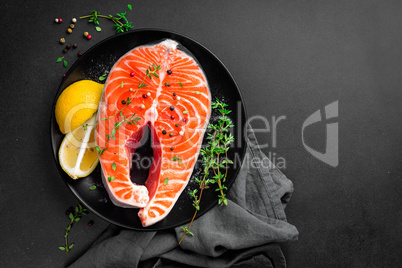Salmon fish steak on black background copy space top view