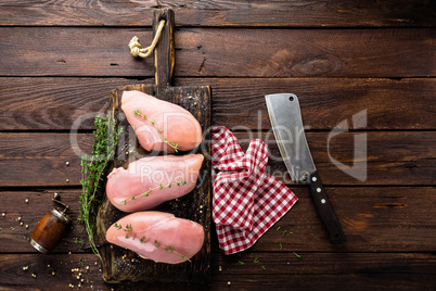 Raw chicken breasts fillets with thyme and spices on wooden cutting board on rustic background copy space directly above