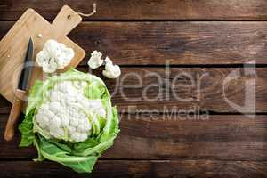 Fresh whole cauliflower on wooden rustic background, top view