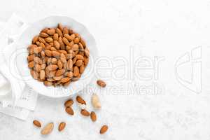 Almond nuts on white background directly above copy space flat lay