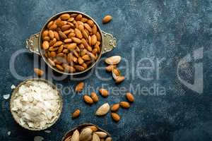 Almond nuts on dark background directly above copy space flat lay