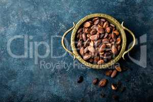 Cocoa beans on dark background, top view, copy space, flat lay