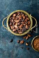 Cocoa beans and powder on dark background, top view, copy space, flat lay