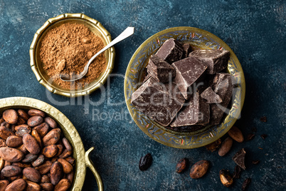 Dark chocolate pieces crushed and cocoa beans, culinary background, directly above