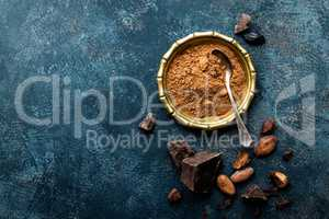 Cocoa powder, beans and dark chocolate pieces crushed, culinary background, top view