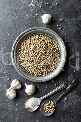 White pepper, garlic and salt on dark grey culinary background, various spices, directly above, flat lay, copy space