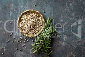 White pepper and fresh rosemary twigs, culinary ingredients on dark background, copy space