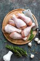Raw uncooked chicken legs, drumsticks on wooden board, meat with ingredients for cooking, top view