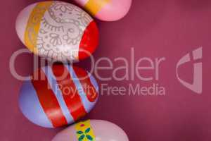 Various Easter eggs arranged on pink background