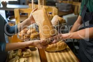 Smiling female customer receiving a parcel from bakery staff at counter