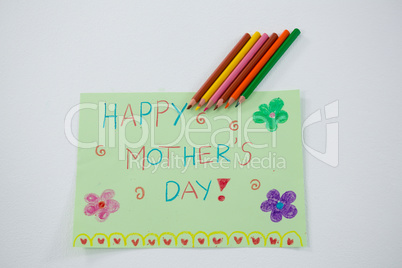 Color pencil kept on happy mothers day greetings card