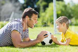 Father and son lying on grass in the park