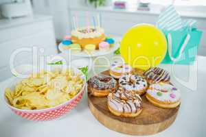 Doughnuts, potato chip, birthday cake and balloons on table