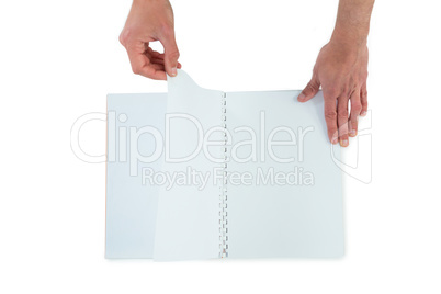 Hands turning pages of blank book