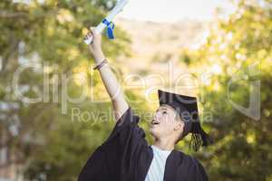 Excited graduate schoolboy with degree scroll in campus