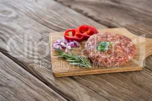 Beef patty and ingredients on wooden tray against wooden background