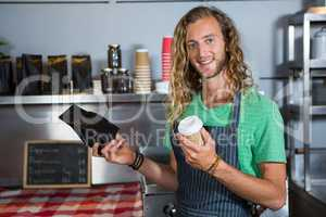 Portrait of male staff holding coffee cup and parcel bag at counter