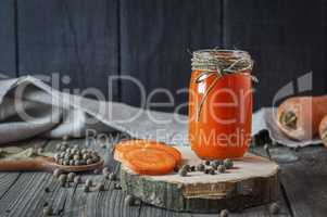 Glass jar with juice on a wooden surface