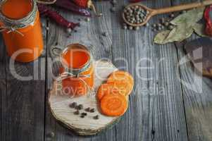 Glass jars with juice on a gray wooden background