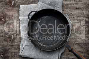 Empty black cast-iron frying pan on a textile napkin