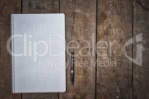 empty open notebook with pen on brown wooden surface