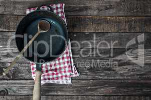 Black frying pan with a wooden spoon on a brown wooden surface