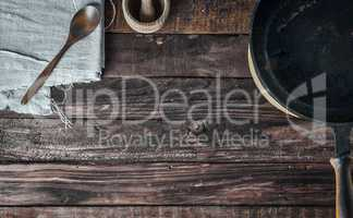 Brown wooden background with black frying pan and wooden spoon