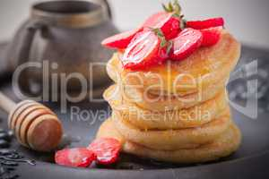 Stack of sweet pancakes with strawberry and honey.