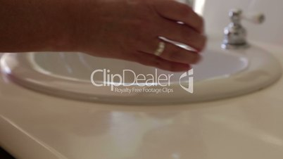 Panning of Effervescent Cold Tablets Dropping Into a Water Glass Near Bathroom Sink
