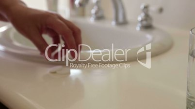 Panning Slow Motion Effervescent Cold Tablets Dropping Into a Water Glass Near Bathroom Sink