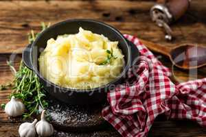 Mashed potatoes, boiled puree in cast iron pot on dark wooden rustic background