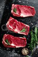 Raw meat, beef steak on black background, top view
