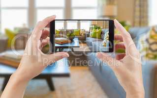Female Hands Holding Smart Phone Displaying Photo of House Inter