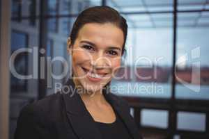 Beautiful businesswoman standing in corridor of office