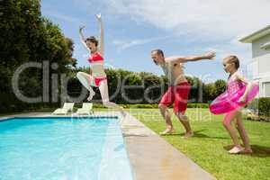 Happy parents and daughter jumping in swimming pool