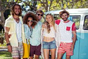 Happy friends standing together with arms around near campervan