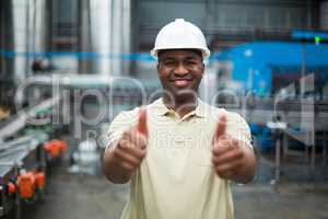 Happy factory worker showing his thumbs up in drinks production plant
