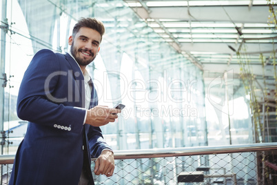 Smiling businessman using mobile phone at railway station