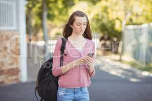 School girl with schoolbag using mobile phone in campus