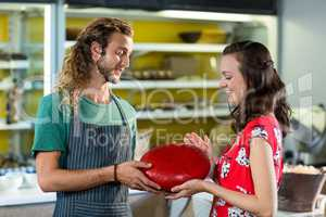 Salesman assisting costumer in buying gouda cheese at counter