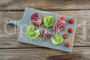 Sirloin steak, cherry tomatoes and cabbage leaves on board against wooden background