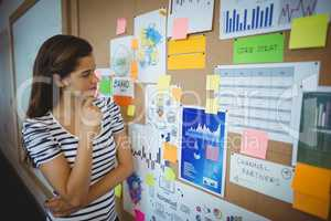 Female executive looking at bulletin board