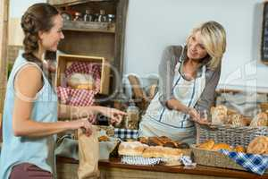 Smiling female customer interacting with bakery staff at counter
