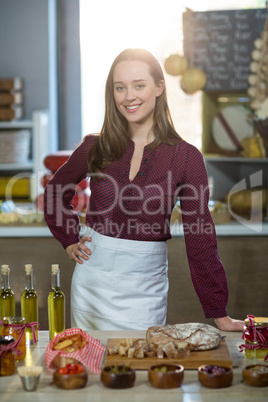Shop assistant standing at the counter with oil bottle, pickle and bread