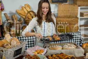 Smiling female staff placing croissant on tray at counter