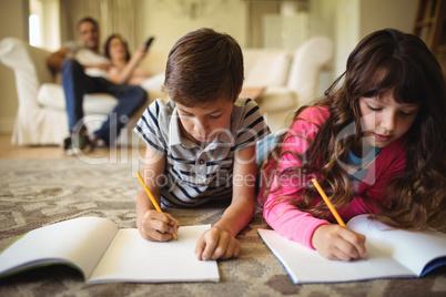 Kids homework while lying on rug