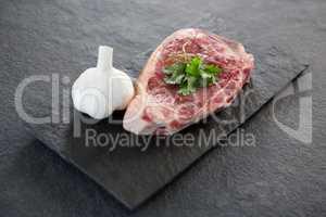 Sirloin chop and garlic on slate plate
