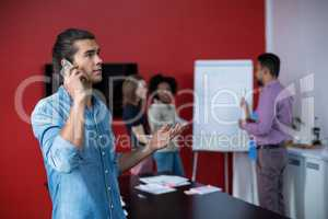 Business executive talking on mobile phone at meeting
